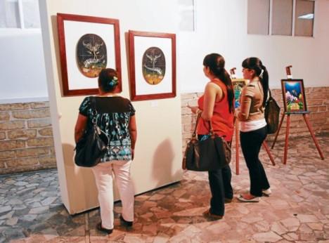 """Asistentes a la muestra observan la obra """"El danzar de Maraita"""", elaborada en lienzo y acrílico, con raíces de café."""